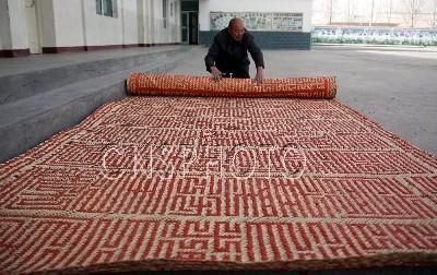 3月24日,新疆库车县的王祖峰将制作好的巨幅九叠篆屏风装卷起