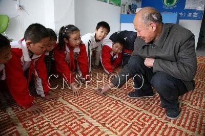 3月24日,新疆库车县的王祖峰在该县第七小学向小学生讲解巨幅九叠篆屏风制作过程